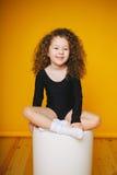 Смешной курчавый смех маленькой девочки в студии на оранжевой предпосылке Стоковая Фотография RF