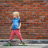 Смешной маленький конькобежец с скейтбордом перед уроком стоковое изображение rf