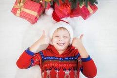 Смешной маленький ребенок с обоими большими пальцами руки вверх как знак сходства Стоковая Фотография