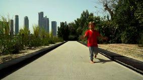 Смешной мальчик бежит и скачет на след батута в парке видеоматериал