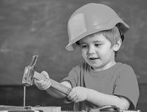 Смешной мальчик бить молотком ноготь молотком Ребенк пробуя новое искусство Индивидуальная уча концепция стоковое изображение