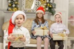 Смешной мальчик держит подарок рождества Стоковые Фото