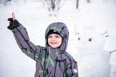 Смешной мальчик маленького ребенка делая снеговик и есть морковь, играя имеющ потеху с снегом, outdoors на холодный день Активное Стоковые Изображения RF
