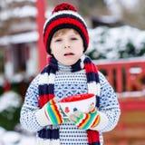 Смешной маленький ребенок держа большую чашку с снежинками и горячим choco Стоковые Изображения RF