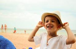 Смешной мальчик в соломенной шляпе на пляже Стоковое фото RF