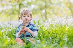 Смешной мальчик есть зайчика шоколада на празднике пасхи Стоковая Фотография