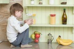 Смешной мальчик ребенка сидя на кухонном столе Стоковые Изображения RF