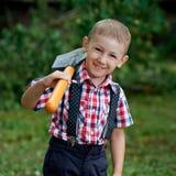 Смешной мальчик с лопаткоулавливателем в саде Стоковые Фото