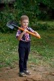 Смешной мальчик с лопаткоулавливателем в саде Стоковые Изображения RF