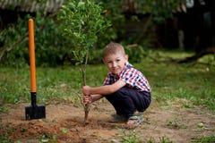 Смешной мальчик с лопаткоулавливателем в саде Стоковая Фотография