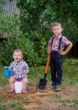 Смешной мальчик с лопаткоулавливателем в саде Стоковые Изображения