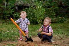 Смешной мальчик с лопаткоулавливателем в саде Стоковое Изображение RF