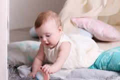 Смешной младенец в белом платье играет с игрушкой на поле Стоковые Фото