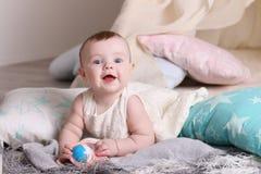 Смешной младенец в белом платье усмехается с игрушкой на поле Стоковое Изображение RF