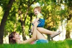 Смешной младенец с мамой в парке лета greenl Стоковая Фотография