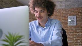 Смешной молодой работник офиса с вьющиеся волосы печатая на компьтер-книжке и сидя на таблице в современном офисе, усмехаясь видеоматериал