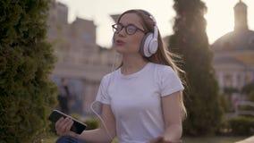 Смешной молодой студент сидя на траве в парке и слушая к музыке в больших наушниках Девушка поя вперед сток-видео