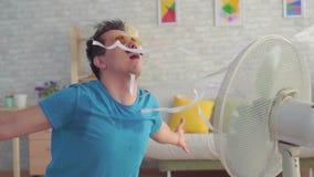 Смешной молодой человек с электрическим вентилятором наслаждаясь холодным ветером в его квартире медленном mo сток-видео