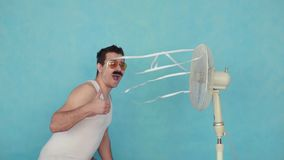 Смешной молодой человек с электрическим вентилятором, наслаждаясь прохладным ветерком показывая большие пальцы руки вверх на голу видеоматериал
