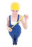 Смешной молодой привлекательный построитель женщины в workwear с животиками измерения Стоковые Изображения