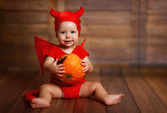 Смешной младенец в костюме хеллоуина дьявола с тыквой Стоковое фото RF