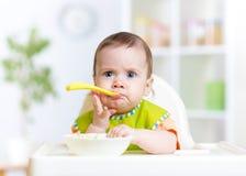 Смешной младенец есть еду на кухне Стоковое Изображение