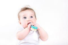 Смешной младенец играя с щеткой волос стоковая фотография