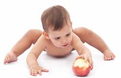 Смешной младенец играя с яблоком. Стоковые Изображения RF