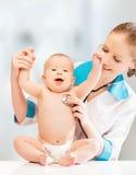 Смешной младенец и педиатр доктора. доктор слушает к сердцу Стоковые Фотографии RF