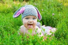 Смешной младенец наслаждаясь зеленой травой Стоковое Изображение