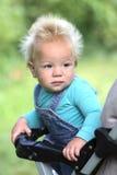 Смешной младенец сидя в кресло-коляске на летний день Стоковые Фото
