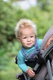 Смешной младенец сидя в кресло-коляске на летний день Стоковое Изображение