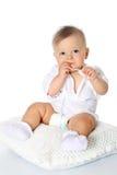 Смешной младенец сидя на подушке и всасывает палец Стоковое Фото