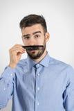 Смешной неполовозрелый парень держа пластичный черный гребень для того чтобы имитировать его поддельный усик Стоковые Фото