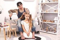 Смешной отец Tattoed времени в крышке и его ребенок играют дома Папа делает волосы его дочери в ее спальне стоковые изображения