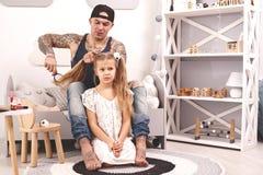 Смешной отец Tattoed времени в крышке и его ребенок играют дома Папа делает волосы его дочери в ее спальне стоковые фотографии rf