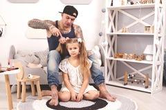 Смешной отец Tattoed времени в крышке и его ребенок играют дома Папа делает волосы его дочери в ее спальне стоковая фотография