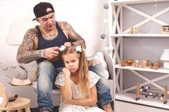 Смешной отец Tattoed времени в крышке и его ребенок играют дома Папа делает волосы его дочери в ее спальне стоковое фото