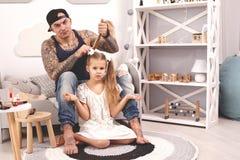 Смешной отец Tattoed времени в крышке и его ребенок играют дома Папа делает волосы его дочери в ее спальне стоковое изображение
