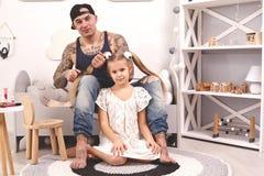 Смешной отец Tattoed времени в крышке и его ребенок играют дома Папа делает волосы его дочери в ее спальне стоковое фото rf