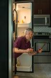 Смешной пакостный человек домовладельца ремонта прибора в холодильнике стоковая фотография rf