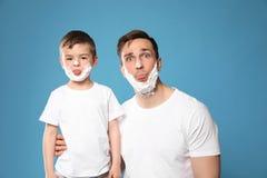 Смешной папа и его маленький сын с брить пену на сторонах стоковое фото