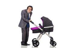 Смешной папа с младенцем и pram на белизне стоковое изображение rf