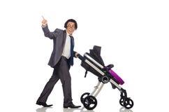 Смешной папа с младенцем и pram на белизне стоковые фото
