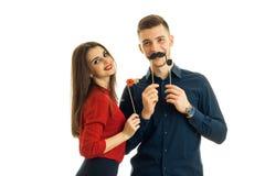 Смешной парень с упорками нося девушки усмехаясь и бумажными для фото Стоковая Фотография RF