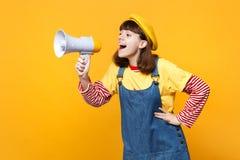 Смешной подросток девушки во французских sundress берета и джинсовой ткани смотря в сторону, клекот в мегафоне изолированном на ж стоковое фото rf