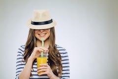 Смешной портрет усмехаясь девушки выпивая апельсиновый сок Стоковая Фотография