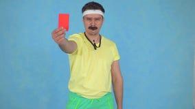 Смешной рассерженный тренер человека со свистком от 80's показывает красную карту на голубой предпосылке акции видеоматериалы
