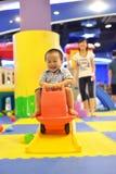 Смешной ребенк в playzone с автомобилем скольжения Стоковая Фотография