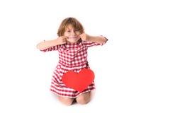 Смешной ребенок девушки в красном платье шотландки с красным бумажным сердцем, Вейл Стоковые Фотографии RF